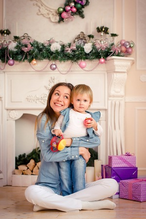 douther: Mother with daughter smiling and hugging, posing at camera in festive studio on background of gifts and stone fireplace decorations Christmas scenery. Lady dressed in denim shirt and white pants, child dressed in sweater, denim vest and navy blue jeans. C