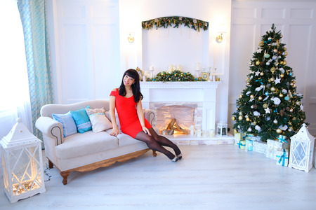 stone fireplace: Female woman smiling and sitting on sofa in middle of bright white studio background Christmas tree with lighted garland, presents and white stone fireplace.  Lady dressed in bright red dress. Concept of New Year party, Christmas presents, winter holidays