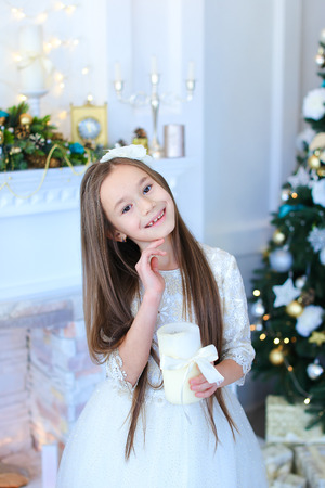 chr: Pretty Little girl child smiling, posing at camera and holding candle on background of white stone fireplace and  decorated Christmas tree with toys and garlands. Girl dressed in white fluffy dress with bow. At head of girl with flower rim. Concept of Chr Stock Photo