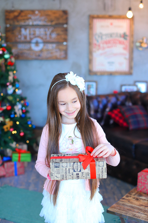 preadolescent: Pre-adolescent Child one girl smiling, looking for gift and holding presents in hands in new year studio. Little girl dressed in bright sweater and fluffy white skirt on top wearing light pink cardigan. At head of girl with flower rim. Concept of Christma