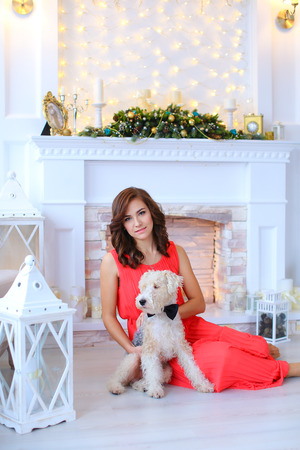 stone fireplace: Beautiful female girl easy smile, sitting on floor and holds beside dog, terrier with black bow tie on white wall with garland and lighted white stone fireplace decorated with Christmas decorations and candles. Girl dressed in long dress coral color. Conc