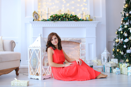 stone fireplace: Young beautiful girl smiling, sitting near white lantern on floor in studio against white stone fireplace decorated with Christmas-tree decorations and Christmas tree beneath which lie Christmas gifts tied with ribbons. Girl dressed in long dress coral co
