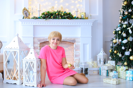 stone fireplace: Beautiful cute female woman sitting on floor near white wooden lanterns and holds golden Christmas tree ball on background of white stone fireplace and lighted Christmas tree beneath which lying in cozy Christmas gifts studio. Woman dressed in pink dress