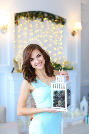 stone fireplace: Young beautiful cute girl smiling, standing and holding lantern in hand on  background of white wall with garland and burning stone fireplace in white light studio. Girl dressed in short dress gentle blue. Concept eve of New Year, Christmas, winter holida Stock Photo