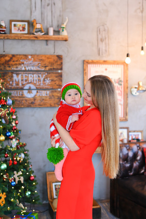 str: Mother and daughter communicate and smile at each other in studio holiday decorations Christmas scenery on background wall with pictures and new year tree.Woman dressed in long red dress, baby wearing red dress with white ruffles, pink tights and long str