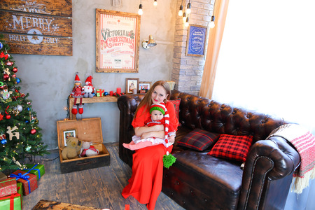 lon: Mother and daughter communicate and smile at each other, sitting on brown sofa in studio holiday decorations Christmas scenery on background wall with pictures.Woman dressed in long red dress, baby wearing red dress with white ruffles, pink tights and lon