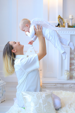 laterns: Young mother with little baby smiling, posing and laughing in decorated Christmas studio on background white wall and laterns. Woman dressed in white shirt and skirt. Boy on back wings and he dressed in white pants and sweater. Concept motherboard care, n