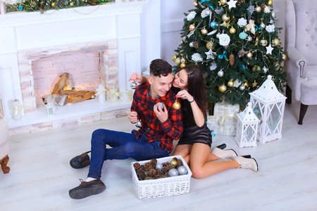 stone fireplace: Young beautiful couple posing on camera, embrace each other, kiss each other and exchange gifts in cozy New Year white studio on background of stone fireplace and Christmas tree. Girl dressed in short dark striped dress, man dressed in checkered red shirt