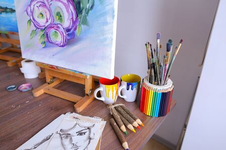 hobbies: Photo works of art, drawing with purple flowers on white canvas on easel written by artist in art studio. Concept of picture written by oil, hobbies and passions, talented peopleadvertising art supplies or school.