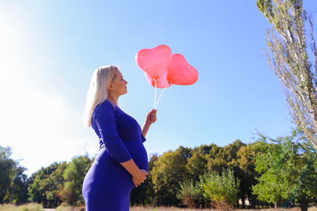 Lovely Young Adult Dirl in Family Way. Blond Woman Luxuriates on Sun and Holds in Hand Three Pink Balloons in Form of Heart, Looks at It, With Care and Affection Stroking Tummy and Enjoys Clear Sunny Day and Life. Lady in Large Park With Trees in Outdoors Stock Photo