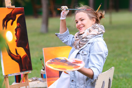 smeared: Young cute woman artist  finishes painting which depicts woman who keeps  sun on orange background, sitting with his back to  photographer and  behind wooden easel, holds palette smeared in paint in large park green day outdoors.Girl dressed in red sweate Stock Photo