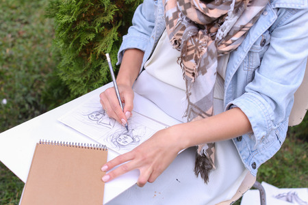 Talented Young Woman Handles Details ,obscures Hair in Picture. Sketch Executed Ordinary Pencil on Sheet of Paper Graphical Way, Which Lying on Wooden Tablet on Artist Knees, Which Located in Park in Open Air. Artist Dressed in White Jacket, Jeans and Che