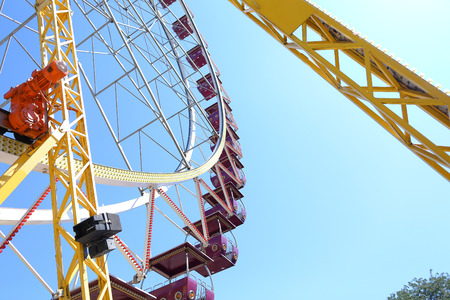 Detail photo of rotating round multicolored ferris wheel with cabins in amusement park against sky.