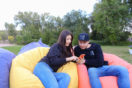 booked: Modern beautiful enamored people, beautiful girl and young man sitting in soft yellow and red chair, planning journey, girl holds phone and talking with boyfriend, booked hotel for total travel, young people smile at each other, located in large green par