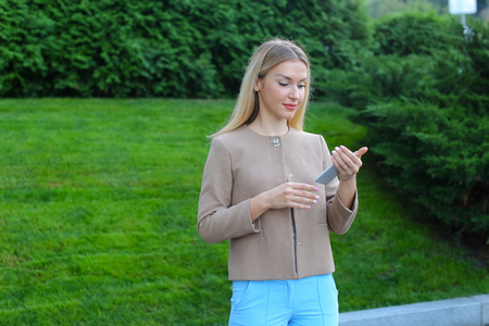 correspondencia: Pretty blonde european appearance uses smartphone for correspondence with friends, make an appointment, looks at screen of gadget, select gifts for friends and viewing news feed. Girl dressed in light blouse, beige jacket and blue pants and stands on back Foto de archivo