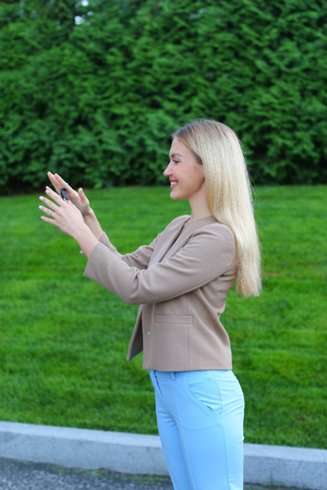 Charming Lady European appearance rejoices acquisition machine or your own apartment, overflowing emotions girl smiling broadly and showing keys. Women with long blonde hair dressed in bright blouse, beige jacket and blue pants, standing on background of