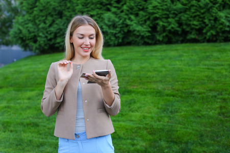 Attractive young woman of european appearance looks at screen and smiles, reads good news or bought long-awaited thing. Girl dressed in light blouse, beige jacket and blue pants, standing on background of green lawn and coniferous plants outdoors. Concept Stock Photo