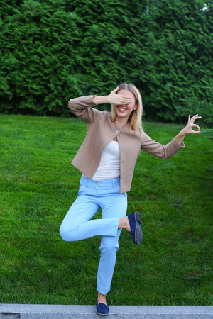 Beautiful blonde shows funny pose, expresses emotions of joy and happiness, fooling around like child having fun and laughing at camera, stands on background of green grass and coniferous trees outdoors. Young lady dressed in light blouse, beige jacket, b