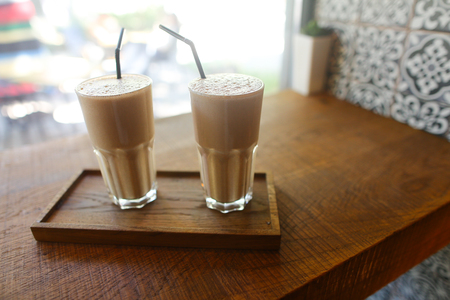 Two coffee beverage latte with crema in glass cup stand with black drinking straw on wooden board on wooden table against window, green flower and wall tiles in coffee shop.Concept of coffee beverages, delicious food, caffeine, catering, cutlery.