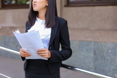 Pretty female girl student holds in hands important paper, Students work or homework, constitutes plan and stands against backdrop of modern business center.Woman with black hair, dressed in white blouse and classic jacket with black skirt and heels.Conce Banco de Imagens