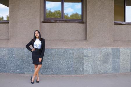 Ambitieux jeune femme moderne, femme d'affaires, étudiant posant pour caméra, souriant, change de posture debout sur le fond du centre d'affaires à l'extérieur. Femme à cheveux noirs, habillée en chemisier blanc et veste classique avec jupe noire et talons. Concep