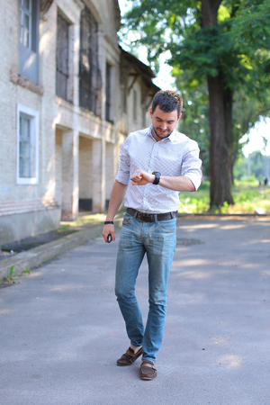loafers: Bearded young men man guy goes, walking along road and looking at watch on arm. Young man dressed in white shirt with red stripe, blue jeans and brown loafers. Concept of business man waiting for meeting, posing in front of camera, casual style.