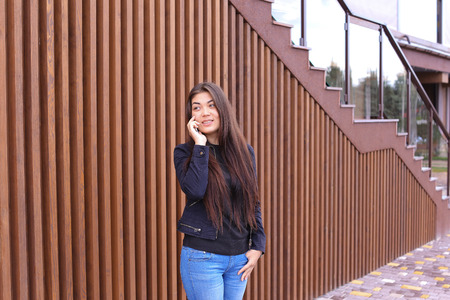 ou: Cute girl with long hair cute talking on phone with friend or loved one, make an appointment. Women dressed in black sweater, blue jeans, black boots on platform and top dressed in jacket standing on background of brown wood panel walls near restaurant ou