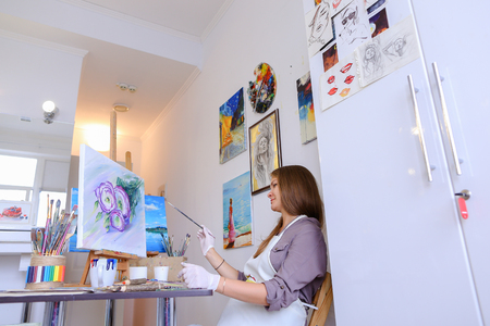 Charming Young Woman Artist Draws Oil Painting With Purple Flowers on a White Canvas, Female Enjoying Favorite Work, Hobbies, posing  for camera and Painting Picture to Order or Gift. Woman With Long Light Brown Hair Dressed Sht Pale Purple Jacket, White
