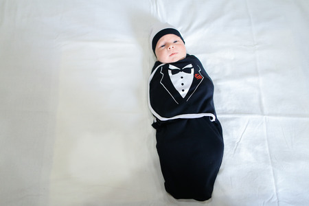 cognicion: Newborn boy in funny childrens business suit and hat lies on white bed in bedroom. Concept of Maternal Love, Affection, Beginning Life, Cognition Surrounding World.