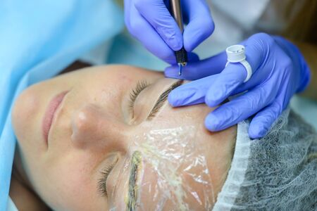 Young blonde woman professional, engaged in reconstruction work responsibly, eyebrows manual method performs procedure, using thinnest needle and maniples, draws most natural eyebrow, side by side on couch and ready for client procedure in cosmetic white