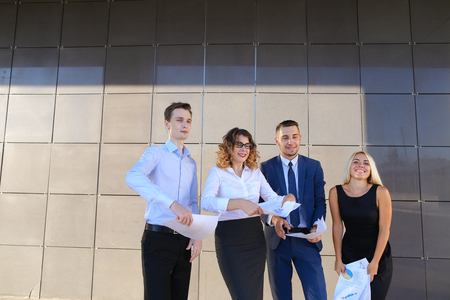 jovenes empresarios: Four beautiful perspective people, two men and two women, young entrepreneurs, students, communicate, solve important problems, share of business ideas, make plans, hold in hands, consider and reading important documents, papers, smiling, laughing, posing Foto de archivo