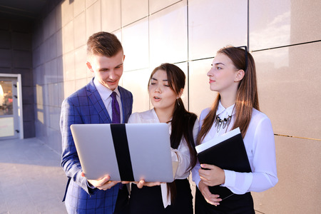 new business problems: Modern young man and two attractive smart young women, business people, students communicate, holding laptop and study work plan, familiarize with presentation, teach each other new programs, solve important problems and workloads holding folder with docu