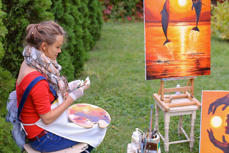 Artist cleans workplace, evaluate work that stands on easel, smiling, posing and looking in camera, sits on chair near paintings in park outdoors on background of coniferous plants in afternoon. Girl dressed in red sweater, dark jeans, white apron and che