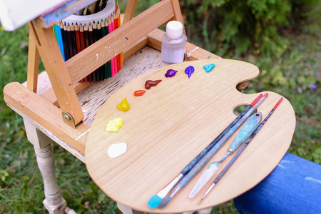 craftmanship: Photo depicts wooden easel on which stands white canvas with painting started, Wooden palette with paints and bank decorated with colored pencils which stands with brush located in park outdoors. Concept of art materials, oil or acrylic paint, professiona