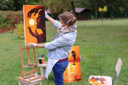 Female European appearance artist evaluates picture and removes from easel, holds and posing with picture which depicts woman with sun in hands made orange smiling and standing in full growth on background of lawn and angered by conifers in large park in  Stock Photo