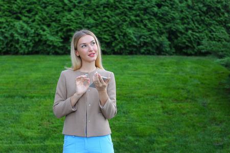 Stylish young girl of european appearance views all around and smiles little smile, thinking about something pleasant. Girl dressed in light blouse, beige jacket and blue pants, stands on background of green lawn and coniferous plants outdoors. Concept of