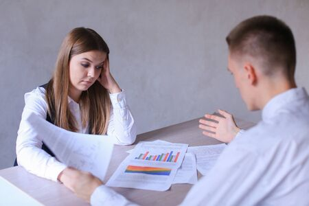 introducing: Guy and Woman Discus Work, Documents and Charts. Young Manager of Firm Man of European Appearance With White Hair in White Shirt Talks About New Business Plan of Employee of Company Young Worker Woman of European Appearance With Brown Long Hair in White B Stock Photo