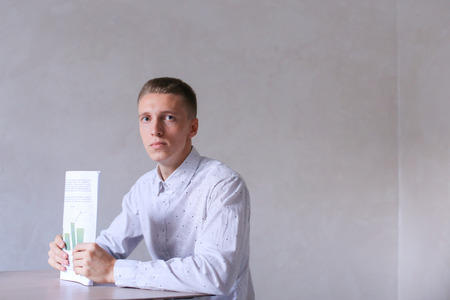 adds: Entrepreneur adds documentation and completes work day, seriously looking into camera. Men with short hair and blond hair sitting on chair at white table in office and dressed in white classic shirt. Concept of businessman office work, sedentary routine w
