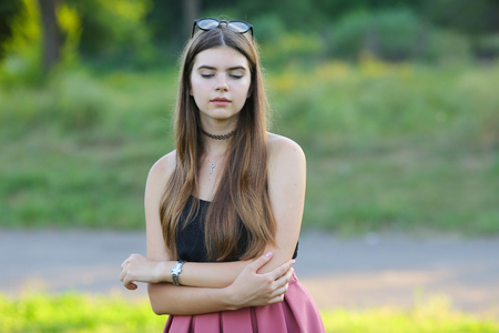 seriousness: Woman with long hair and beautiful eyes on a green background shows the different human emotions. Lady portrays grief, seriousness, sadness Stock Photo