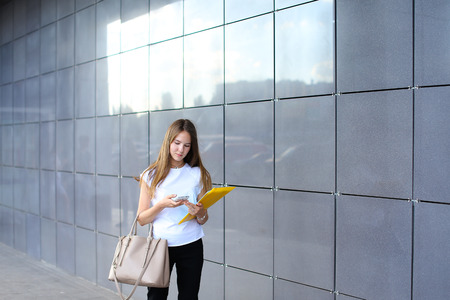 hait: Pretty young successful female entrepreneur girl uses mobile phone, solves problems, holds documents on background of gray wall of business center. Girl with long hait dressed in white shirt, black pants and keeps on hand beige bag. Concept of business me