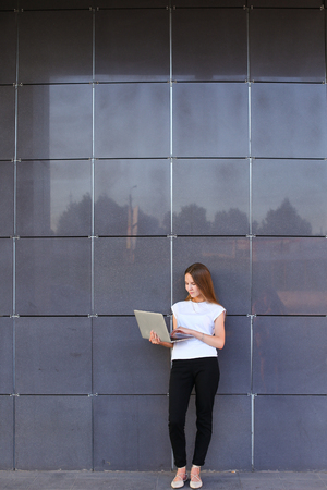promising: Promising young entrepreneur beautiful woman uses laptop for work, make appointment, solves important business issues and and stands right in all growth against the background of gray wall of modern business center. Girl dressed in white shirt, black pant