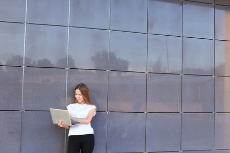 hait: Beautiful young female woman girl entrepreneur successful person holds laptop in hands works, solves problems, and stands on background wall of modern business center.Girl with long hait dressed in white shirt and black trousers.Concept of business meetin
