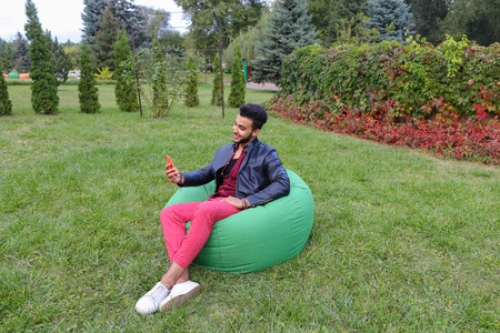 Young Handsome Man Arab Businessman, Student Holding Mobile Phone, Gadget and Calls, Communicates on phone For Video Calling, Smiling and Sitting in Comfortable Green Chair in Garden Outdoors. Bearded Man With Dark Hair Dressed in Black T-Shirt, on Top Ma