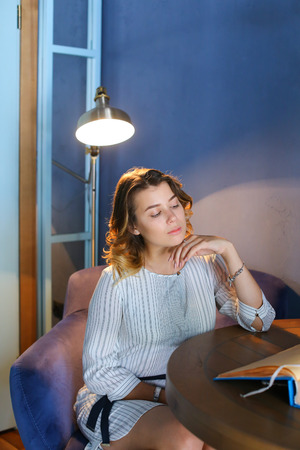 downcast: Wonderful elegant young adult female girl woman looks away with downcast eyes, holds hand near face and sits in purple chair at table on background of gray lighted lamp and blue walls in beautiful stylish modern restaurant. Girl with blond curly hair sitt