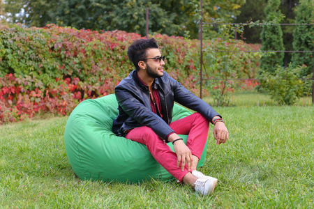 Arabian Young Man Sitting and Resting From City Bustle in Soft Green Chair, smiles and Looks Around. Handsome Guy Has Dark Hair and Black Beard and dressed in Maroon Shirt Over Black Leather Jacket and Bright Pink Jeans and White Sneakers Accessories From