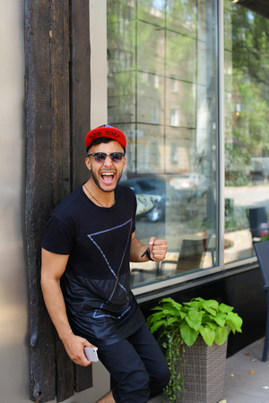 concep: Handsome happy young man arab stands near wall smiles, rejoices and holds in hand mobile phone on background of panoramic windows in modern restaurant. Man dressed in dark T-shirt, black pants, white sneakers and black red color cap and sunglasses. Concep