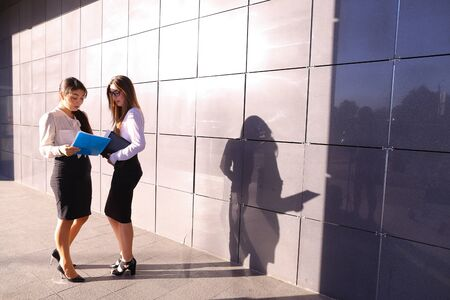 dealt: Two beautiful girls successful young business woman student discussing work plans, dealt with, reports, plan next month, communicate with each other, solve important problems and stand on background of gray wall of bussiness center outdoors. Girl with dar