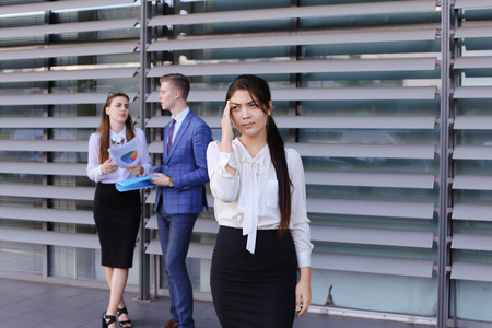 work took: Attractive young perspective business woman, student rests, took break from work, posing at camera, holds on head from fatigue and stands on background of colleagues who discuss workflows, consider paper near of business center outside. Girls with light b