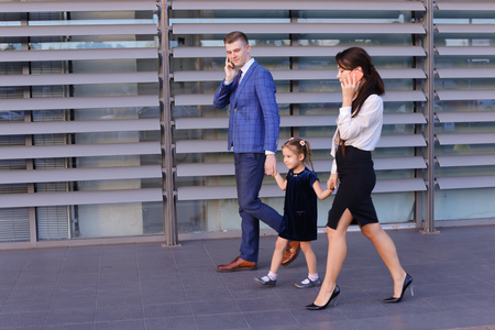 revisando documentos: Successful young handsome male man young father and modern girl, young mother hold gadgets  in hand, mobile phones and talking on them, solve operational issues, agree to meet, negotiate with business partners, reviewing documents in hurry to work and kee