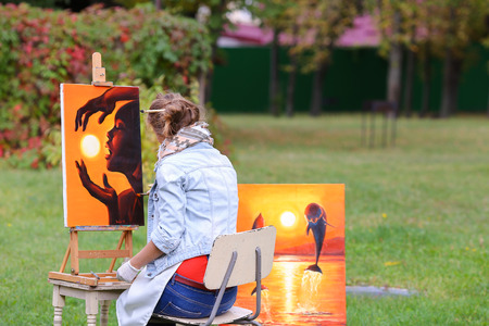 Young cute woman artist  finishes painting which depicts woman who keeps  sun on orange background, sitting with his back to  photographer and  behind wooden easel, holds palette smeared in paint in large park green day outdoors.Girl dressed in red sweate Stock Photo
